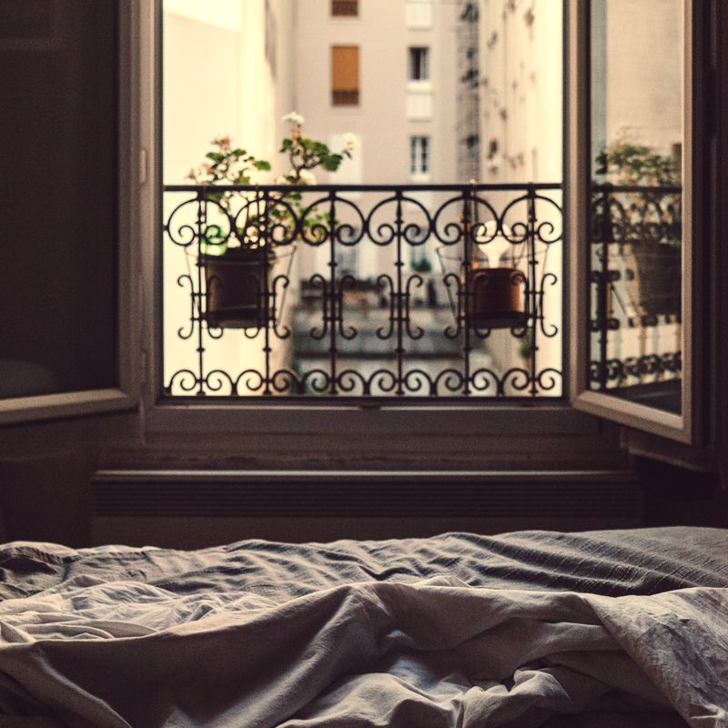 a bed with lilac crumpled linens with view out a Parisian window